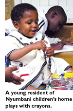 A young resident of Nyumbani children's home plays with crayons