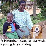 A Nyumbani teacher sits with a young boy and a dog