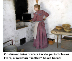 Costumed interpreters tackle period chores. Here a German 'settler' bakes bread.